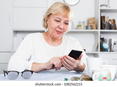 Mature woman enjoys a modern smartphone while sitting at home at a table