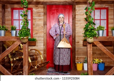 Mature woman in ethnic costume standing on the porch of a wooden house. Full length portrait. Rural style, decoration.