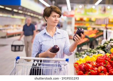 Mature woman examines a eggplant  in vegetables section of the supermarket