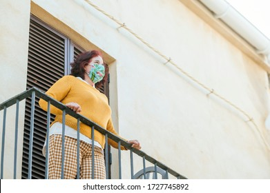 Mature woman with face mask on balcony