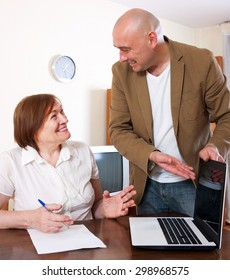 Mature woman filling questionnaire for employee with laptop of the bank