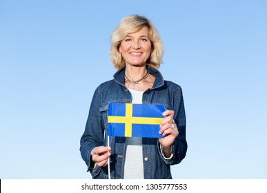 Mature woman with the flag of Sweden against the background of the blue sky.