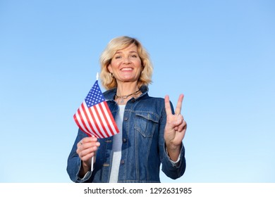Mature woman with the flag of the United States of America against the blue sky. US flag in female hands.