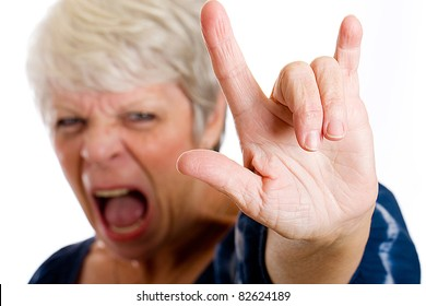 Mature woman giving a rock and roll hand sign while screaming.