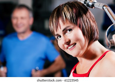 Mature woman in the gym lifting weights on a lat pull machine, exercising