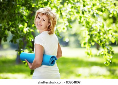 Mature woman with a gym mat outdoors