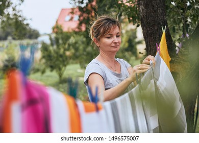 Mature woman hanging a freshly laundered bed linen on clothesline stretched between two trees in a orchard. Candid people, real moments, authentic situations