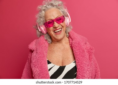 Mature woman with happy expression, wears wireless headphones, enjoys favorite playlist ad listens music, feels free and relaxed, spends time at home, dressed in fashionable outfit, models indoor