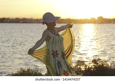 Mature woman, with hat playing with a handkerchief by the sea  in the wind by the sea at sunset, next to the salt flats  in the Mar Menor, Murcia, Spain, holidays, milf, holidays,
