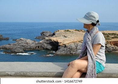 Mature woman with hat and scarf sitting observing the sea at Cabo de Palos, Murcia, Spain, Spain, holidays, milf,