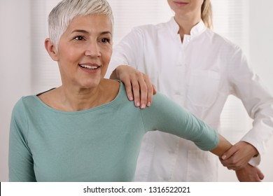 Mature Woman having chiropractic back adjustment. Osteopathy, Physiotherapy, Sport injury rehabilitation concept, holistic care