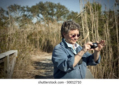 Mature woman having fun with her small digital camera on vacation, hiking and birdwatching in a national park.