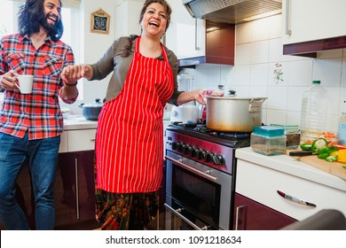 Mature woman is having fun making a curry at home with company from her mid adult son.