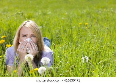 Mature woman with hay fever and handkerchief lying in the meadow