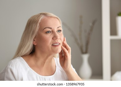 Mature woman with healthy skin at home