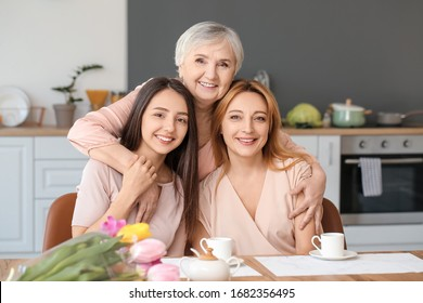 Mature woman with her adult daughter and mother spending time together at home