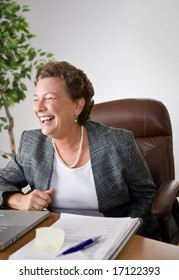 Mature woman at her desk in an office laughing uproariously.