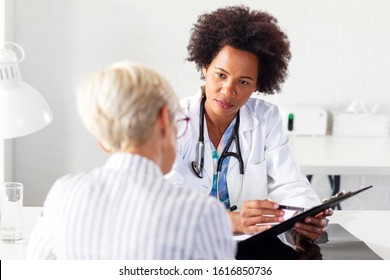 Mature woman with her doctor in ambulance talking about healthcare