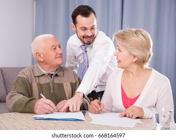 Mature woman and her eldery father signing contract with smiling credit manager at home