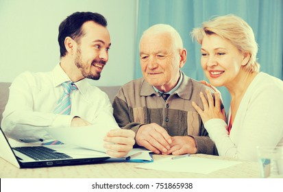 Mature woman and her eldery father studying agreement conditions with smiling manager
