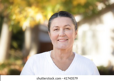 Mature woman in her sixties standing outside on a bright autumn day