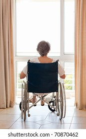 Mature woman in her wheelchair with her back to the camera