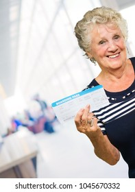 Mature Woman Holding Boarding Pass, Indoors