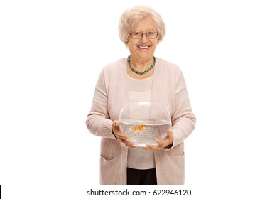 Mature woman holding a bowl with a goldfish inside and looking at the camera isolated on white background