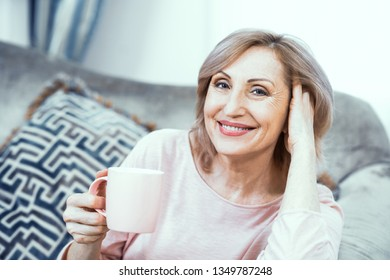 Mature Woman Holding Cup Of Coffee While Sitting On Sofa. Relaxing After Yoga Exercises. Home Relax Concept.