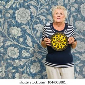 Mature Woman Holding Dart Board On Wallpaper