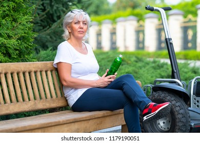 Mature woman holding green bottle while sitting on wooden bench next to unmoving self balancing transporter in front of tall bushes during summer month