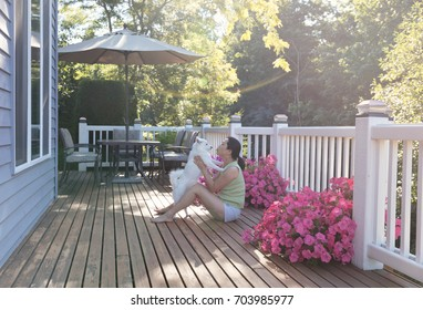 Mature woman holding her family dog while outdoors on home deck during bright summer morning with lens flare