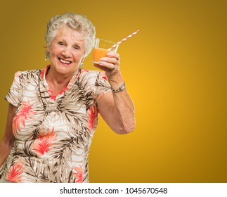 Mature Woman Holding Juice Glass Isolated On Yellow Background