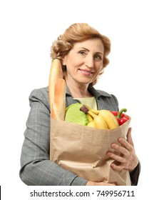 Mature woman holding paper bag with groceries on white background