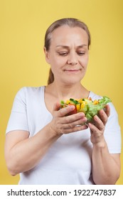 Mature woman holding a plate of vegetable salad. Studio shot on a yellow background. Healthy food concept