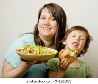 mature woman holding salad and little cute boy with hamburger teasing close up, family food unhealthy