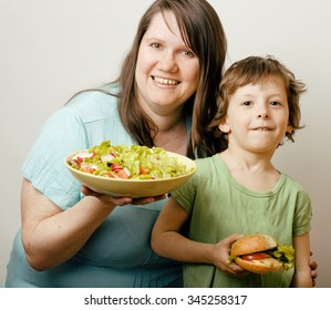 mature woman holding salad and little cute boy with hamburger teasing close up, healthy family