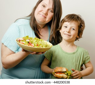 mature woman holding salad and little cute boy with hamburger teasing close up, family food