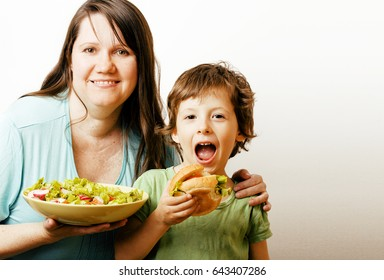 mature woman holding salad and little cute boy with hamburger
