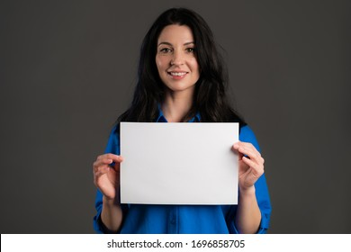 Mature woman holding white a4 paper poster. Copy space. Smiling trendy lady with long hair on studio background.