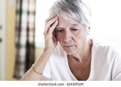 A Mature woman at home touching her head with her hands while having a headache pain