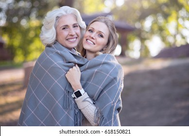 Mature woman hugging aged mother at the picnic