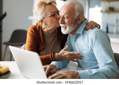 Mature woman kissing her mature husband while he uses a computer at home