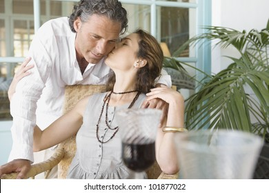 Mature woman kissing man while having a red wine drink at home.