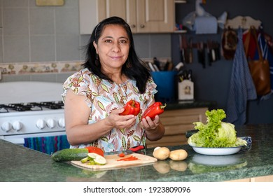 Mature woman in kitchen choosing vegetables to cook - Hispanic mom smiling cooking fresh organic salad in her kitchen - Shutterstock ID 1923809096