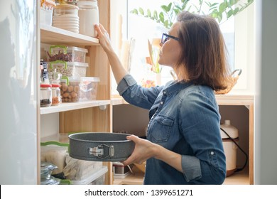 Mature woman in the kitchen pantry with products. Storage wooden stand with kitchenware, products necessary to cook.