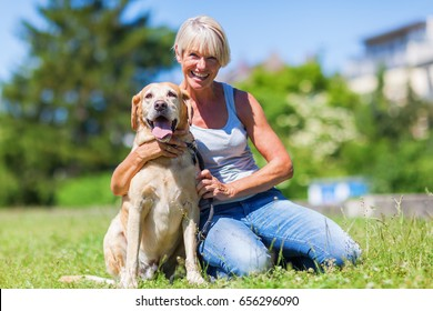 mature woman with a labrador retriever sitting on the lawn