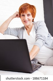 Mature woman with  laptop. Female with computer at home