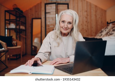 Mature Woman with laptop sitting at table and talking in glamping camping tent. Modern vacation lifestyle concept.