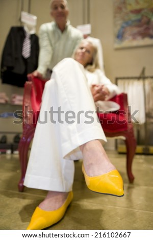 Mature Woman With Legs Crossed In Chair By Man Close Up Of Feet